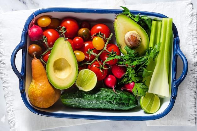 Helle mehrfarbige frische sommergemüse und -früchte auf einem tisch in einem backblech. kochen, salatzutaten