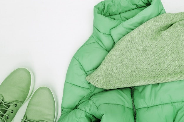Helle mode kleidet die tendenz, die auf weißem hintergrund mit kopienraum gefärbt wird. strickschal, komfortlederstiefel und warme daunenjacke. flach lag mit warmer frauenkleidung. ansicht von oben.