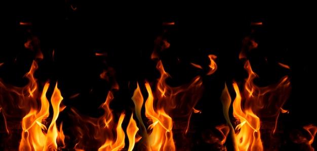 Helle orange und gelbe flammen auf einem schwarzen hintergrund