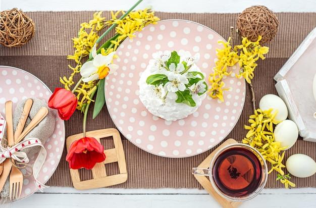 Helle osterkomposition mit hausgemachtem osterkuchen auf einem teller, blumen, tee, eiern. osterferienkonzept.