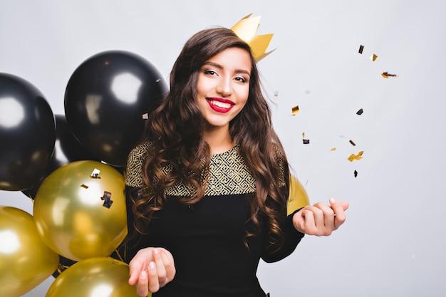 Helle partei der freudigen jungen frau im eleganten schwarzen kleid der mode und der gelben krone, die neues jahr feiern,