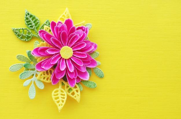 Helle rosa büttenpapierblume und gelbe und grüne blätter auf einem hellen gelben hintergrund. leerzeichen zum kopieren.