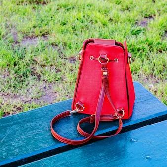 Helle rote handtasche steht auf einer blauen holzbank.
