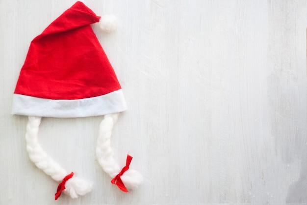 Helle rote santa claus-hüte auf einem weißen hölzernen hintergrund. neujahrskarte.