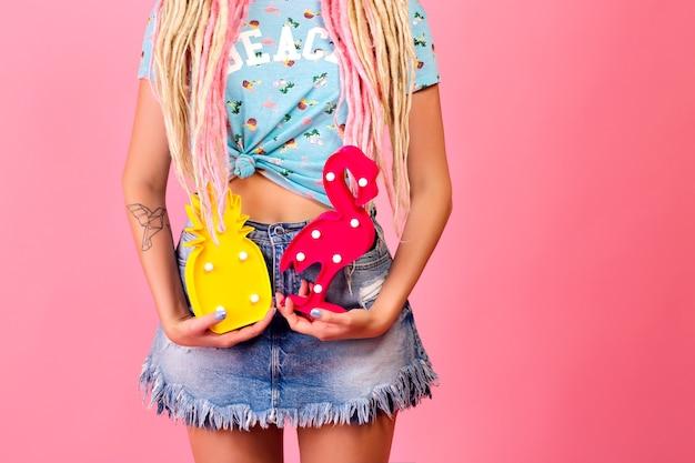 Helle sonnige modedetails, junge frau, die dekorative ananas und flamingo hält
