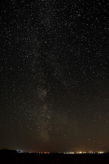 Helle sterne am nachthimmel über der stadt mit straßenbeleuchtung