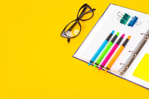 Helle stifte, gläser und notizbuch liegen lokalisiert auf gelbem hintergrund