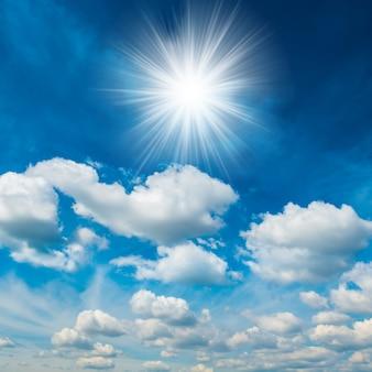 Helle strahlende sonne mit weißen, flauschigen wolken am blauen himmel. natur hintergrund