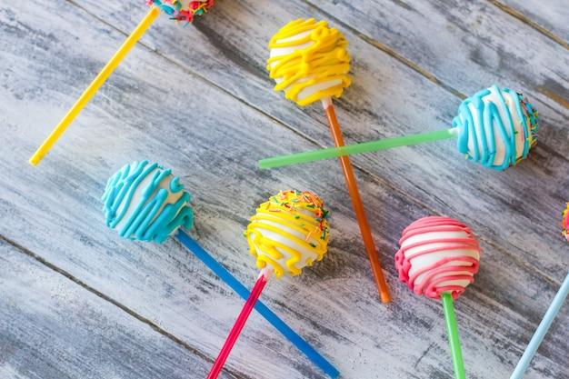 Helle süßigkeiten auf stöcken. süßigkeiten auf grauem hintergrund. leckere cakepops. einfache möglichkeit, kinder zu überraschen.