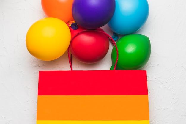Helle tasche und glänzende luftballons in lgbt-farben