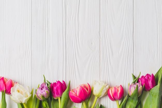 Helle tulpen auf hölzernem hintergrund