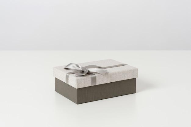 Helle und dunkelgraue geschenkbox mit schleife