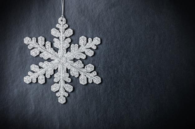 Helle weihnachtsschneeflocke auf schwarzem hintergrund