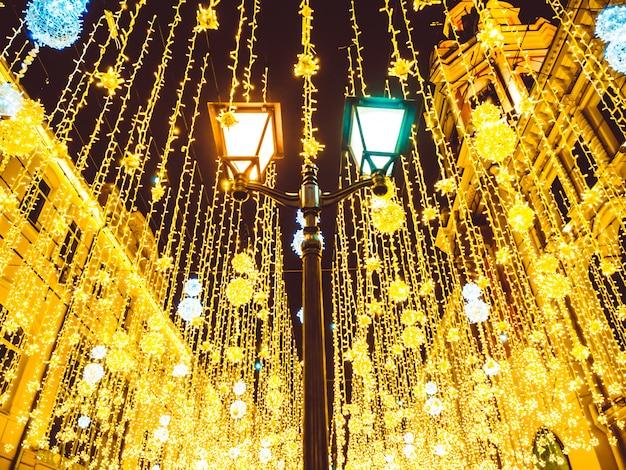 Helle weihnachtsstraßenbeleuchtung an der fassade der gebäude.