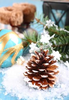 Helle weihnachtszusammensetzung mit pinecone, blauem ball und stiefeln auf schnee