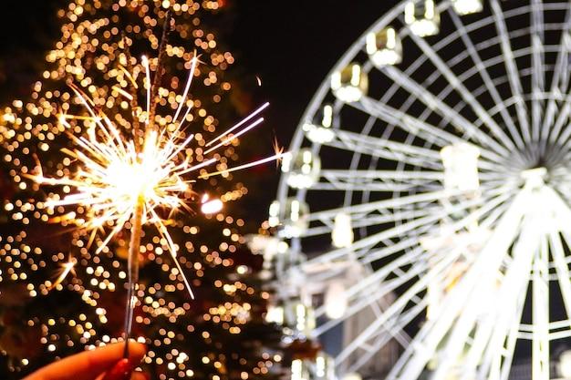Helle wunderkerze gegen festliche weihnachtsbaumlichter und riesenrad des neuen jahres in der nachtstadt