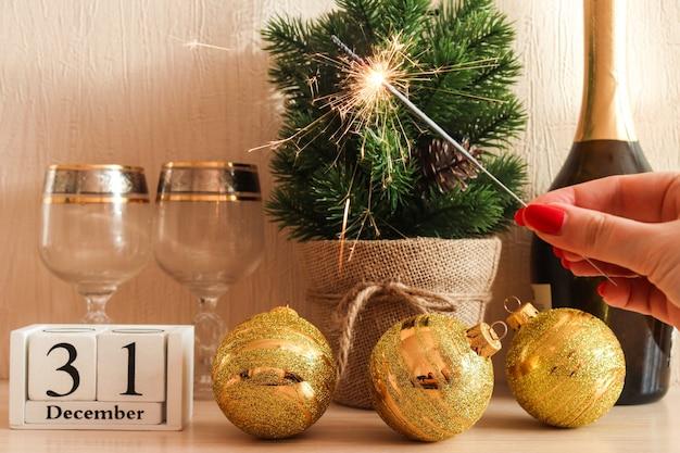 Helle wunderkerze vor festlichem hintergrund des neuen jahres mit champagner-sektgläsern und -kalender