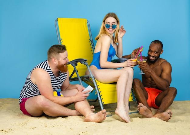 Helle zeit. glückliche freunde, die ruhen, cocktails auf blauem studiohintergrund trinken. konzept der menschlichen gefühle, gesichtsausdruck, sommerferien oder wochenende. chill, sommer, meer, meer, alkohol.