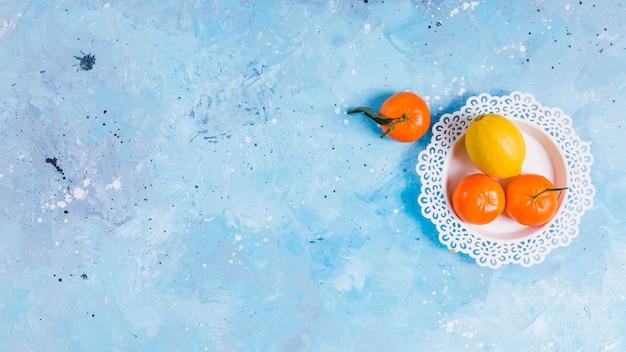 Helle zitrusfrüchte auf spitzenplatte