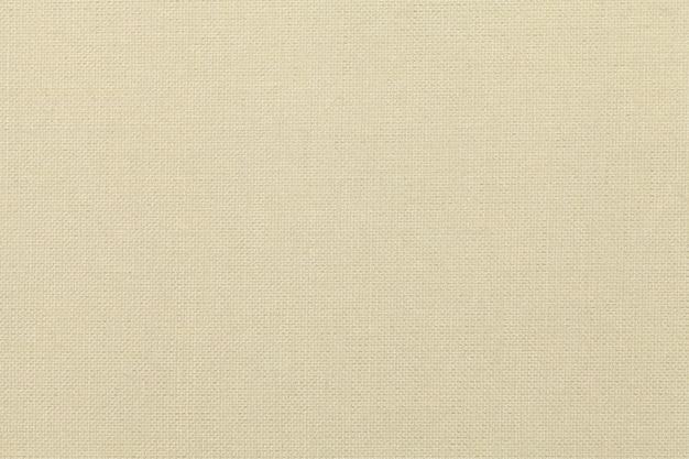 Heller beige hintergrund von einem textilmaterial. stoff mit natürlicher textur.