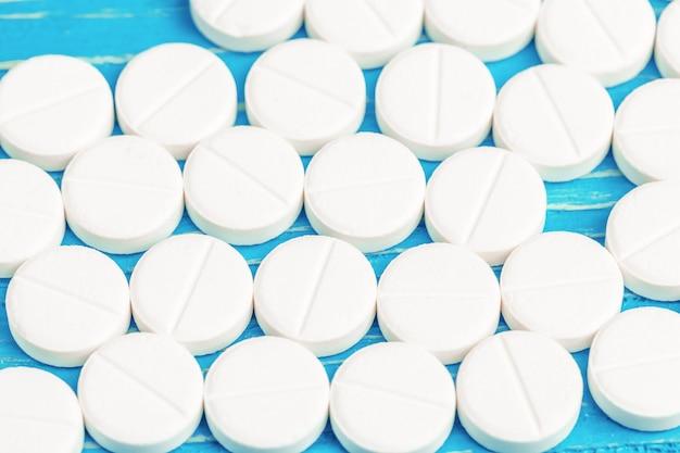 Heller blauer holztisch mit verschütteten weißen tabletten