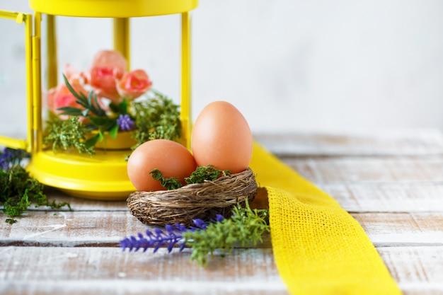 Heller frühling blüht mit ostereiern nahe einer gelben dekorativen laterne