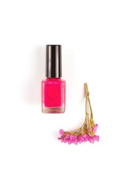 Heller fuchsia nagellack auf einer weißen oberfläche neben einer blume der gleichen farbe