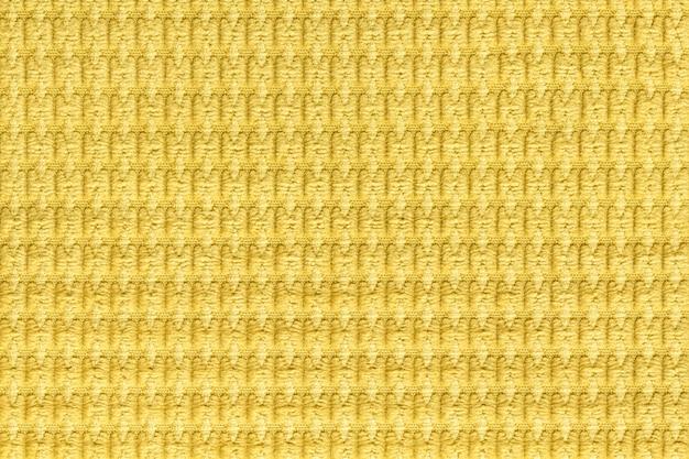 Heller gelber hintergrund vom weichen flaumigen gewebeabschluß oben, beschaffenheit von textilmakro