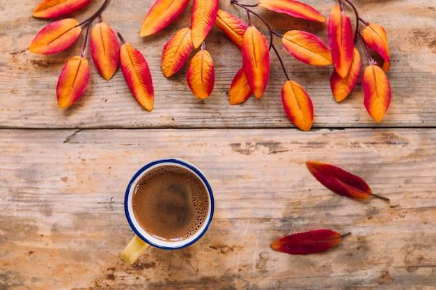 Heller herbstlaub und tasse kaffee auf hölzernem hintergrund