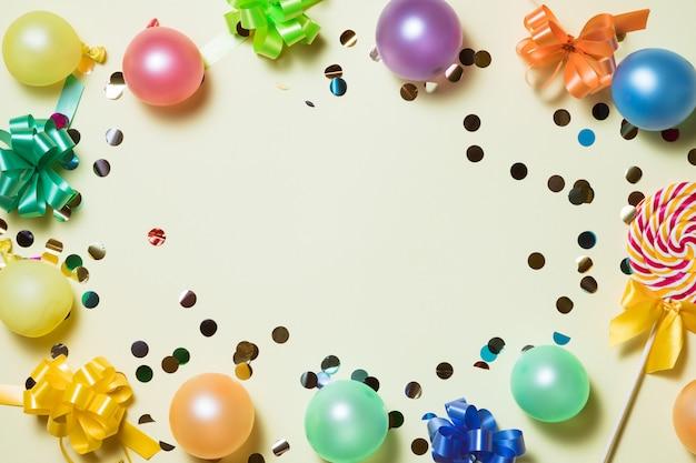 Heller pastellhintergrund der geburtstagsfeier mit ausläufern, konfettis, ballone auf gelbem backround.