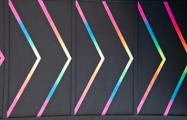 Heller pfeil, der die richtung im abstrakten hintergrund der mehrfarbigen fluoreszierenden malerei anzeigt.