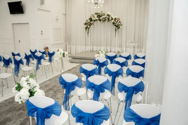 Heller raum für hochzeiten. reihen von gästestühlen mit blauem stoff verziert