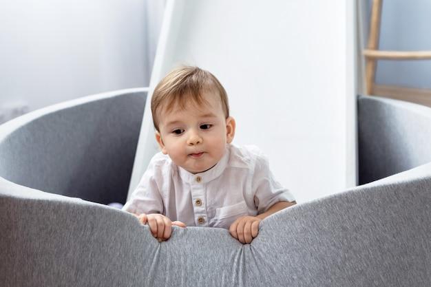 Heller raum. glücklicher junge, der auf dem boden im weichen kinderbecken spielt. junge im weißen t-shirt