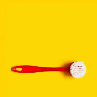 Heller roter pinsel liegt auf einem hellen gelben hintergrund