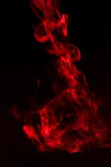 Heller roter rauch bewegt auf schwarzen hintergrund wellenartig