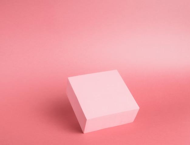 Heller sockel eines würfels auf einem papierhintergrund in rosa