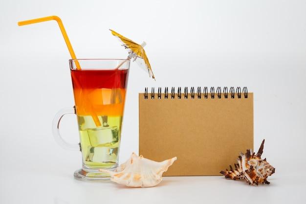 Heller sommercocktail in glas und notizbuch
