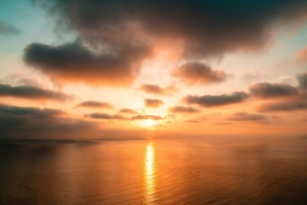 Heller sonnenuntergang mit großer gelber sonne unter der meeresoberfläche
