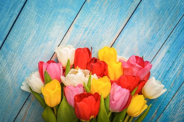 Heller strauß mehrfarbiger tulpen nahaufnahme auf holzbrettern der blauen farbe.