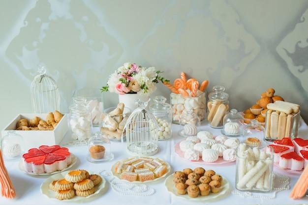 Heller und empfindlicher schokoriegel an einer hochzeit oder an einer party. kekse, süßigkeiten, marshmallows und blumen auf dem tisch