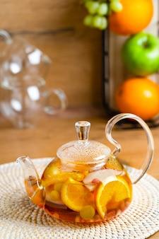 Heller vitamintee mit früchten in einer glasteekanne auf dem küchentisch auf holzhintergrund mit früchten
