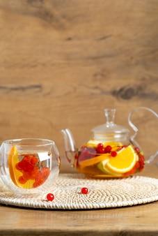 Heller vitamintee mit früchten in einer glasteekanne auf dem küchentisch auf holzhintergrund