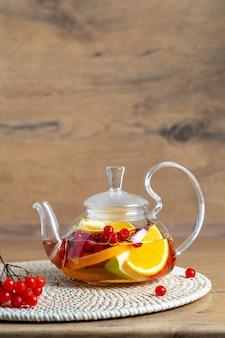 Heller vitamintee mit früchten in einer glasteekanne auf dem tisch auf einer hölzernen hintergrundnahaufnahme