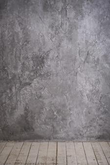 Heller weinlesedachbodeninnenraum mit bretterboden, strukturierter gealterter grauer beton an der wand.