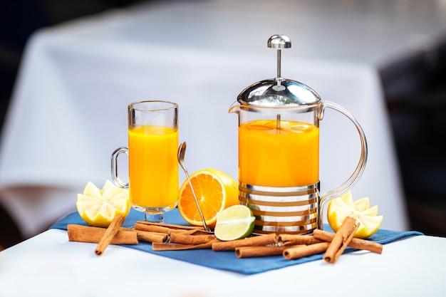 Heller zitrusgelber tee in einer tasse und einer französischen presse mit zimt