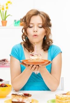 Helles bild der schönen hausfrau mit kuchen und kerze