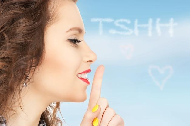 Helles bild einer jungen frau mit finger auf den lippen