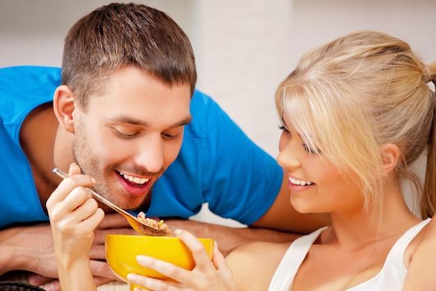 Helles bild eines glücklichen paares mit müsli (fokus auf den menschen)