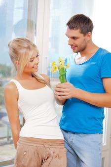 Helles bild eines glücklichen romantischen paares mit blumen (fokus auf frau)