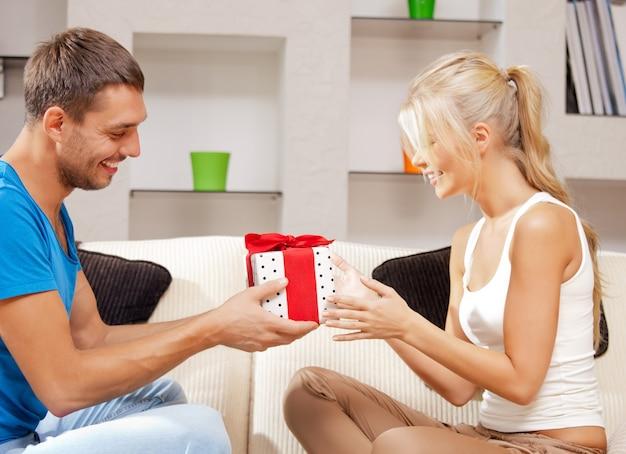 Helles bild eines glücklichen romantischen paares mit geschenk (fokus auf den mann)